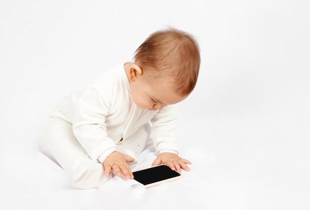 Bambino in possesso di un telefono cellulare isolato su sfondo bianco generazione z
