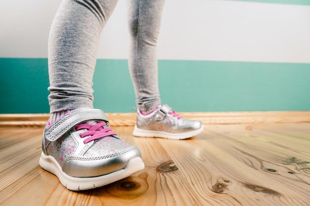Bambino in scarpe da ginnastica su superficie di legno