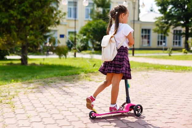 Bambino in sella a scooter sulla via del ritorno a scuola