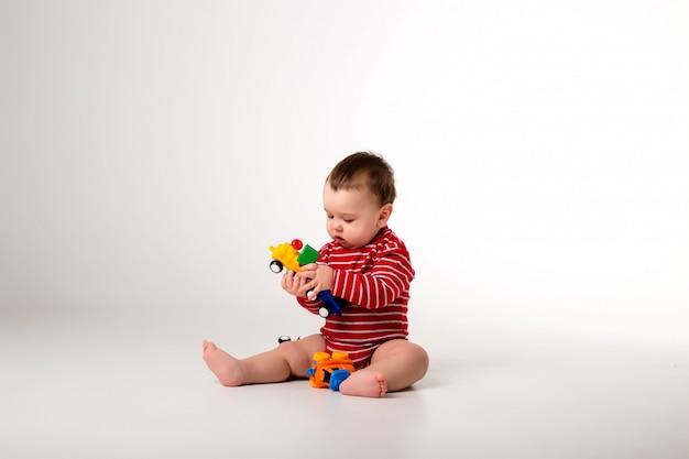 Bambino in tuta rossa seduto a giocare con un giocattolo su un muro bianco
