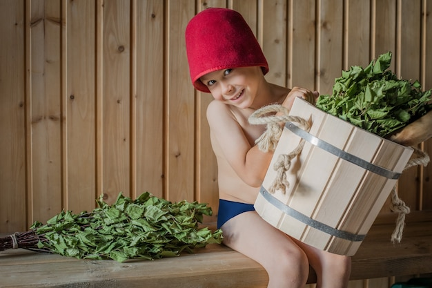Bambino in un bagno russo con una scopa di betulla