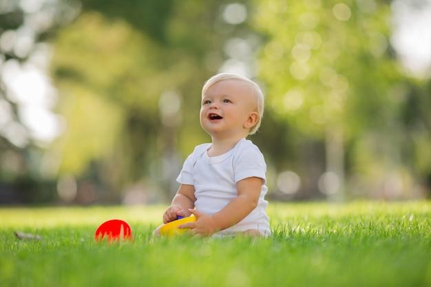 Bambino in un body bianco seduto sull'erba verde giocando