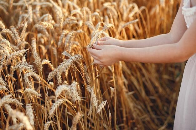 Bambino in un campo di grano estivo. bambina in un vestito bianco carino.