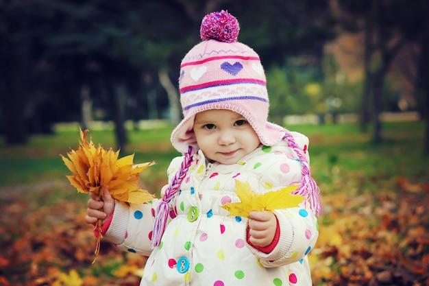 Bambino in un cappotto rosso con foglie d'autunno.