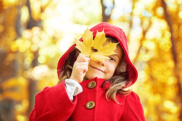 Bambino in un cappotto rosso con foglie di autunno