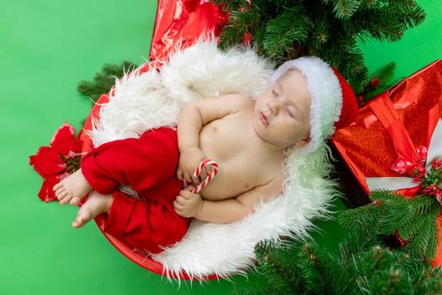 Bambino in un costume da babbo natale sdraiato su uno sfondo verde