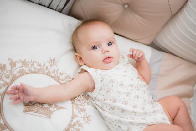 Bambino in un letto su grigio