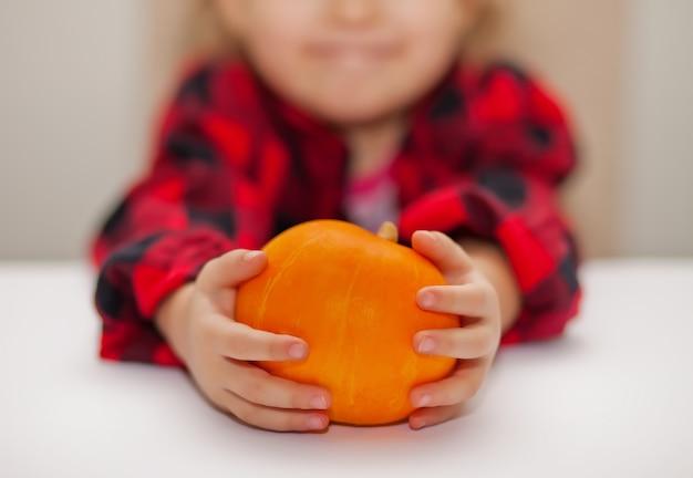 Bambino in una camicia a scacchi tiene una zucca matura nelle mani. concetto di raccolta autunnale