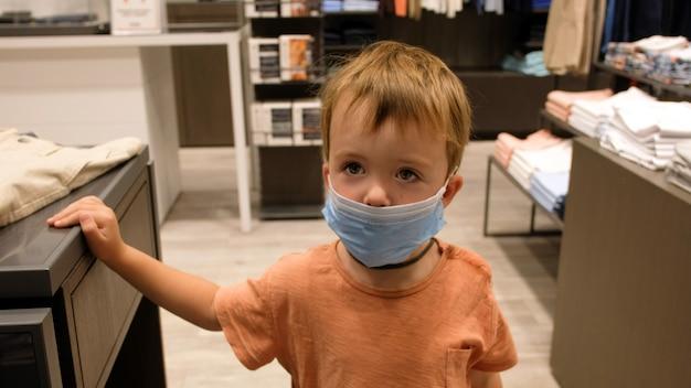 Bambino in una maschera protettiva in un negozio