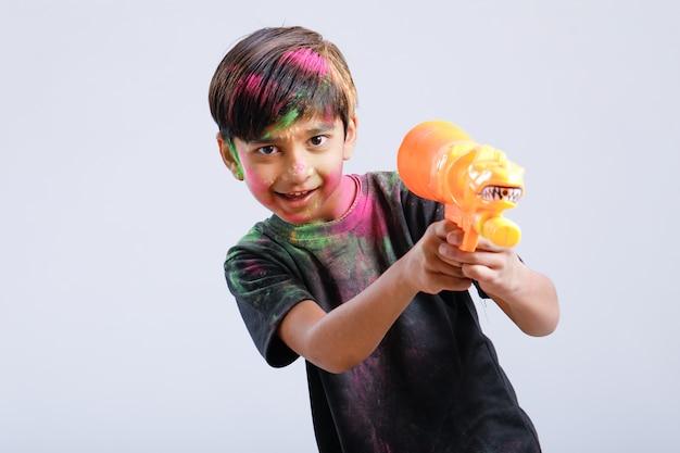 Bambino indiano che gioca holi con la pistola di colore