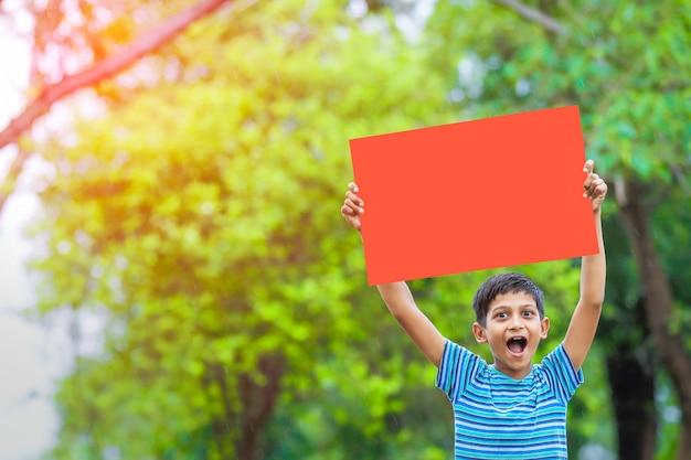 Bambino indiano che tiene manifesto vuoto