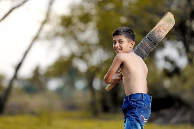 Bambino indiano rurale che gioca cricket