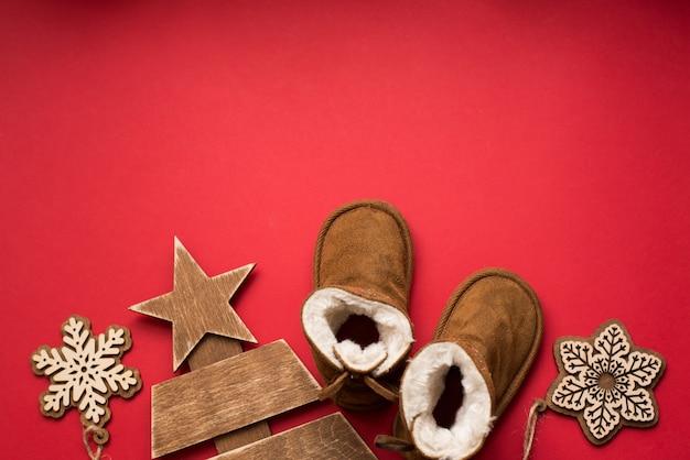 Bambino inverno natale rosso con stivali, albero di legno e fiocchi di neve. vacanze per bambini, copyspace