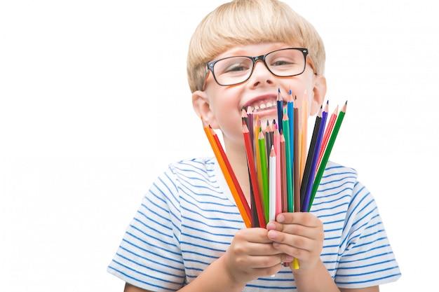 Bambino isolato con matite. adorabile bambino su sfondo bianco. ritratto di ragazzo biondo divertente con matite colorate.