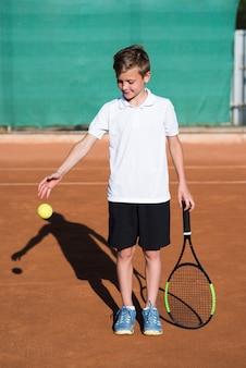 Bambino lungo tiro che gioca con la pallina da tennis