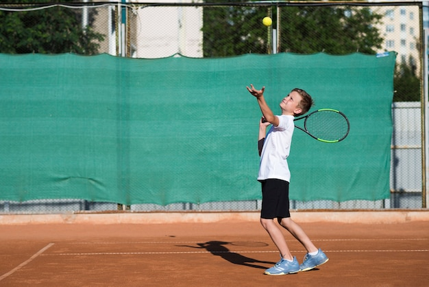Bambino lungo tiro che serve sul campo da tennis