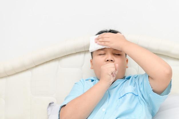 Bambino malato con febbre alta e tosse sul letto,