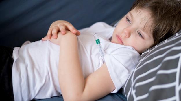 Bambino malato di vista frontale che si siede nel letto