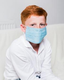 Bambino malato di vista laterale con la maschera facciale