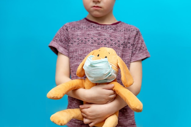 Bambino malato in una maschera con un giocattolo. epidemia di influenza, virus