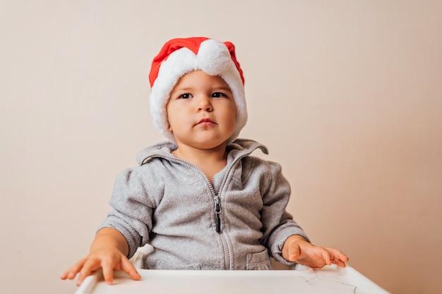 Bambino nel cofano di natale che veste in su la bambola, su fondo bianco. copia spazio