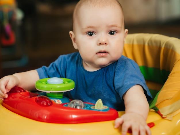 Bambino neonato ragazzo caucasico sveglio in walker