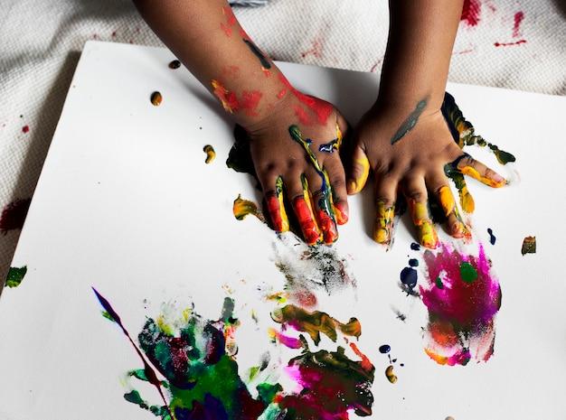 Bambino nero che si diverte a dipingere