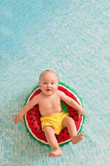 Bambino nuota in un salvagente di un cocomero vicino a una spiaggia di sabbia con palme in riva al mare