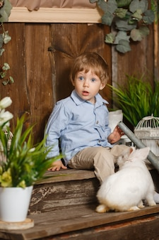 Bambino onesto che gioca con il coniglietto di pasqua in un'erba verde. decorazione rustica. lo studio ha sparato su una priorità bassa di legno