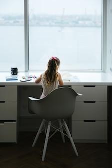 Bambino piccolo che fa a casa compito vicino alla finestra, vista posteriore, concetto di homeschooling
