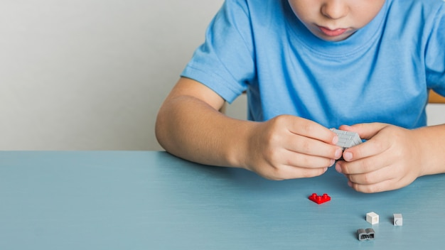 Bambino piccolo del primo piano che gioca con il lego
