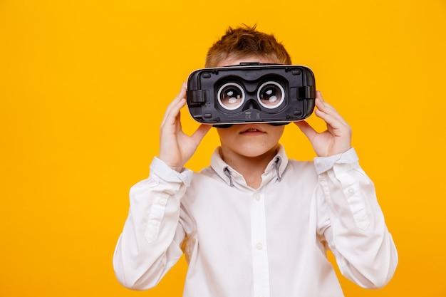 Bambino piccolo in camicia bianca che esamina macchina fotografica tramite la cuffia avricolare di realtà virtuale isolata