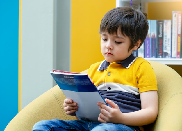 Bambino prescolare che legge un libro con il fronte curioso nella biblioteca con fondo confuso dello scaffale per libri