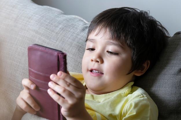 Bambino prescolare con volto sorridente che pone sul divano e giocare sul telefono