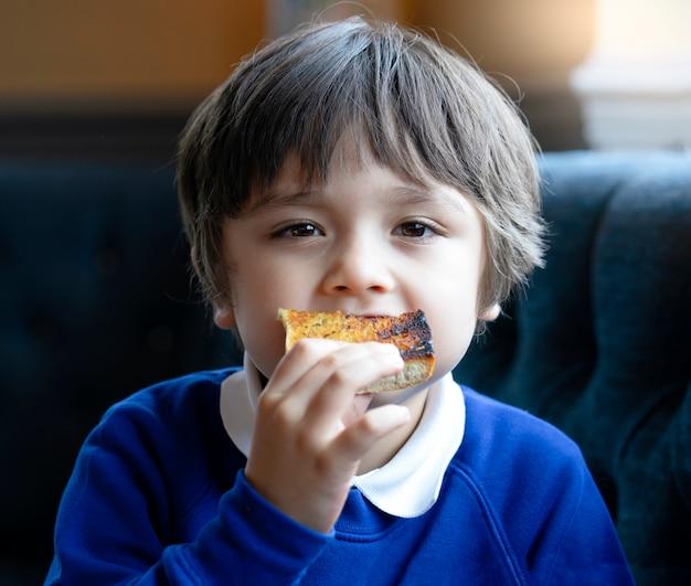 Bambino prescolare mangiare pane all'aglio, little boy mangiare bruciare toast