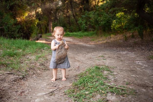 Bambino raccoglie immondizia nella foresta, una bambina porta una bottiglia di plastica