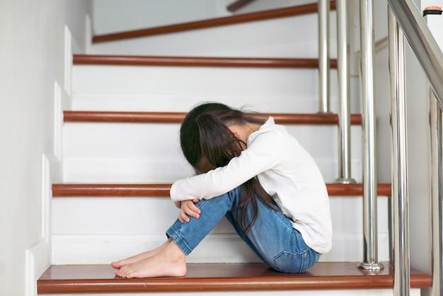 Bambino sconvolto di problema con la testa in mani che si siedono sul concetto della scala