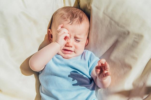 Bambino sdraiato al sole arrabbiato e pianto chiamando i suoi genitori.