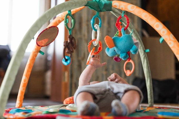 Bambino sdraiato sul tappeto in via di sviluppo con giocattoli educativi mobili