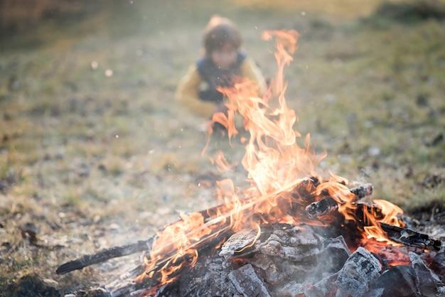 Bambino seduto accanto al fuoco da campo sul prato