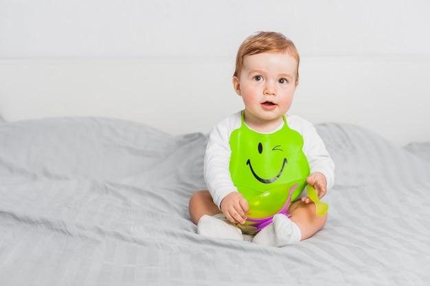 Bambino seduto che indossa pettorina