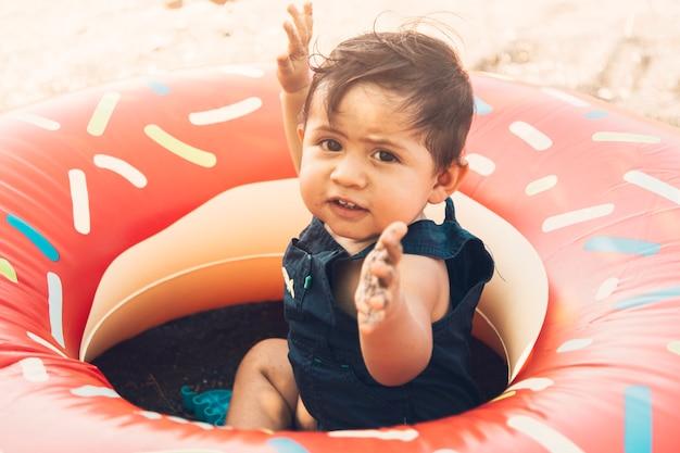 Bambino seduto in cerchio di nuoto