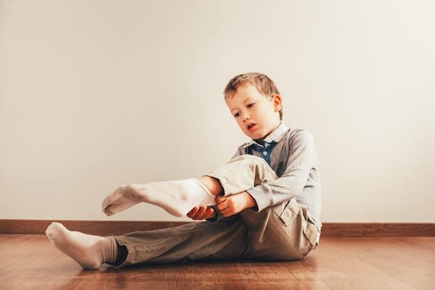 Bambino seduto per terra mettendo i calzini con un'espressione di sforzo, concetto di autonomia.