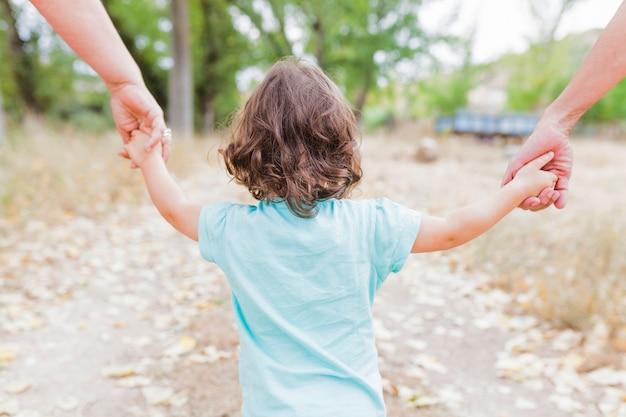 Bambino senza volto che cammina con i genitori