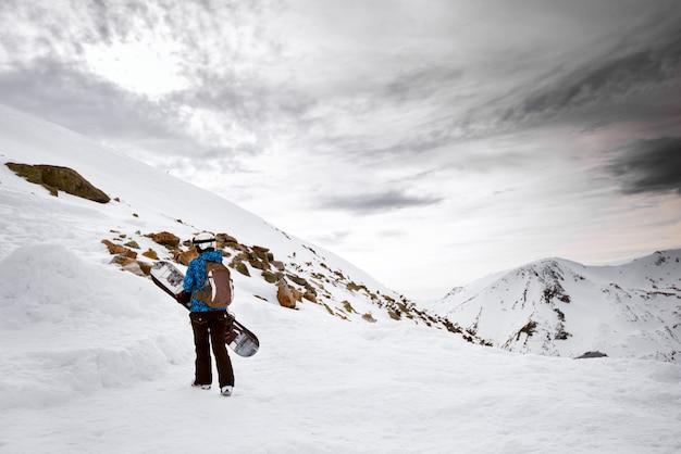 Bambino solo con lo zaino che tiene lo snowboard nella montagna di neve.