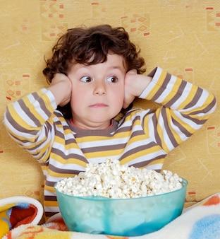 Bambino sorpreso con una ciotola piena di popcorn