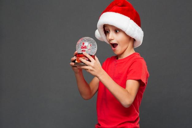 Bambino sorpreso del ragazzino che porta il cappello di santa di natale