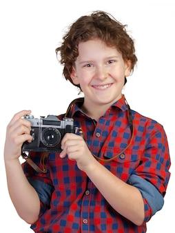 Bambino sorridente allegro (ragazzo) che tiene una macchina fotografica istantanea