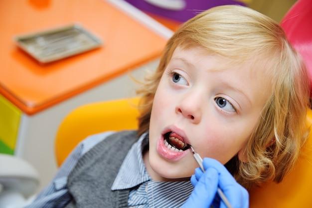Bambino sorridente con capelli ricci chiari su esame nella sedia dentaria