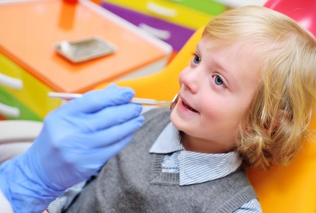 Bambino sorridente con capelli ricci leggeri su esame nella sedia dentale